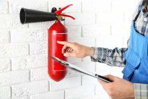Man inspecting the fire extinguisher against white brick wall ba